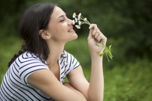 Portrait of the beautiful girl with a flower in the park